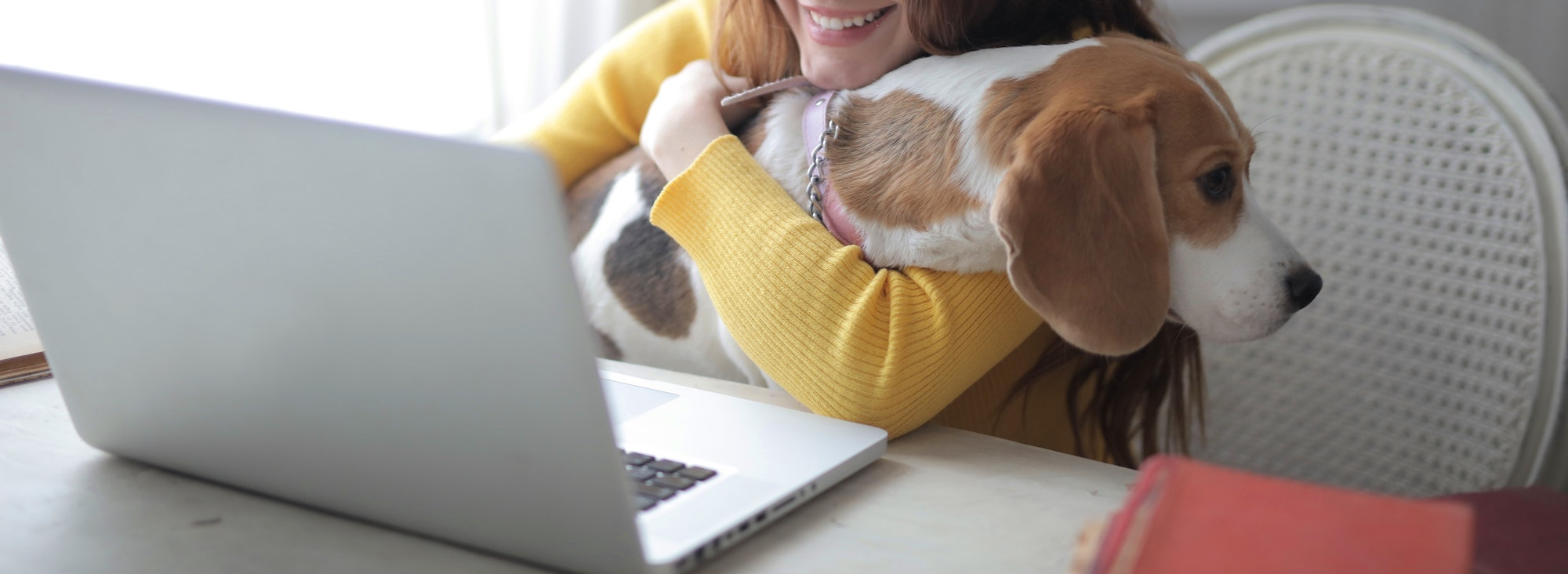 woman cuddling her dog whilst working from home on her laptop