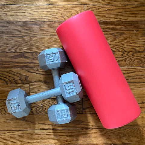 On a wood floor, seen from above, are two gray 15-lb dumbbells, one crossed over the other, and to their right a red foam roller lying on its side.