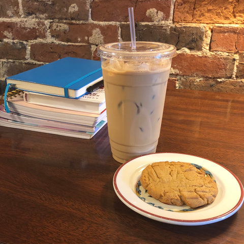 On a table sit a stack of books and notebooks, an iced latte, and a small plate with a cookie on it.
