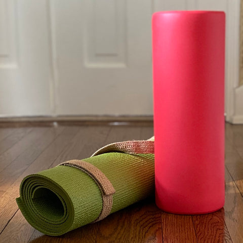 On a wood floor are a red foam roller, standing on end, and to its left a green yoga mat rolled in a tan strap.