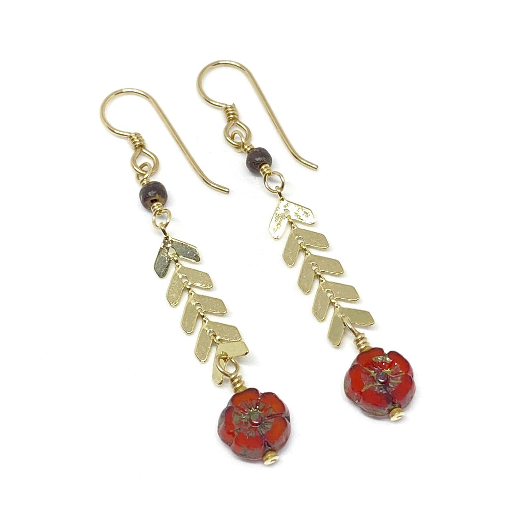 On a white background lies a pair of earrings with gold-toned metal components. Each features a small brown wood bead, below which is a short length of chevron chain, finished with a scarlet flower-shaped bead.