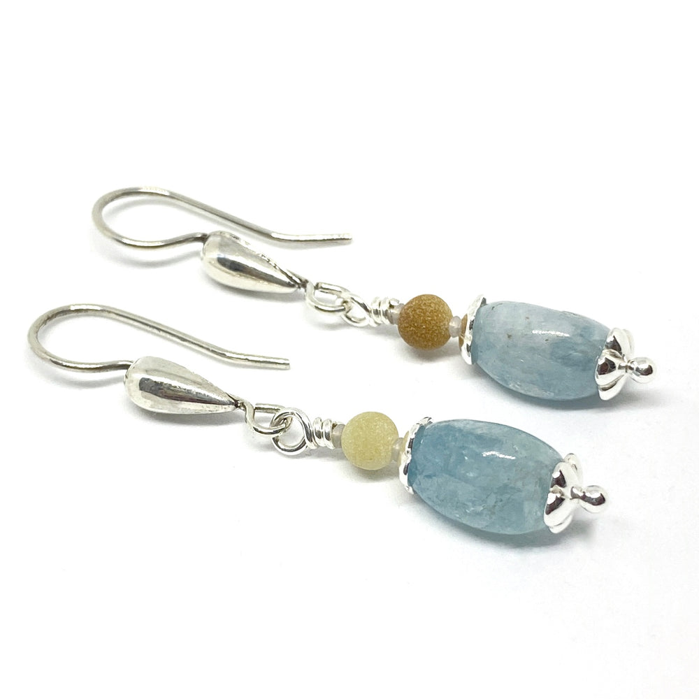 On a white background lies a pair of earrings, earwires to the left. The earrings feature larger beads in a soft blue and smaller ones in yellow and deep tan. The metals are silver-toned.