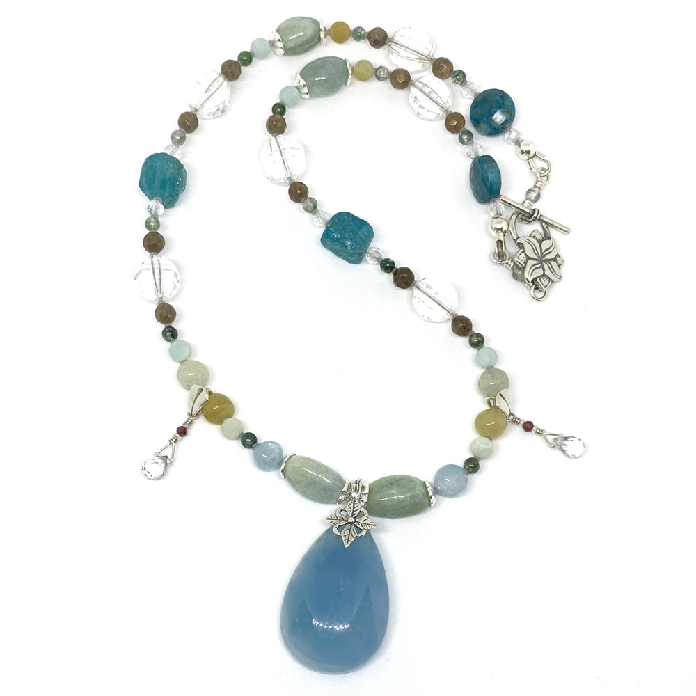 On a white background lies a beaded necklace with a teardrop-shaped blue pendant. The piece features beads in shades of blue, green, yellow, brown, and aqua, and the metal components are silver-toned.