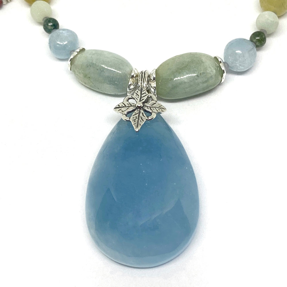 A strand of beads curves down from the upper corners of the photo. In the middle of this strand is a silver-toned, flower-motif bail from which hangs a teardrop-shaped pendant. The pendant is a soft blue; the beads are in shades of blue, green, and yellow.