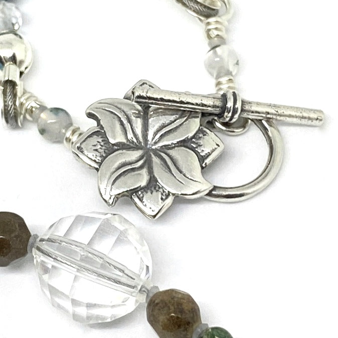 In the center of the photo is a silver-toned toggle clasp with a four-petaled flower atop a diamond shape. Toward the bottom of the photo is a large clear bead with a smaller brown bead to either side.