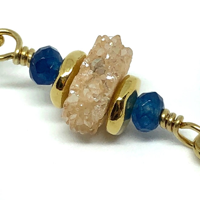 A gold-toned wire link with a wrapped loop at each end is shown on a white background. Next to each loop is a small indigo-colored faceted bead. Between these is a champagne-colored druzy slice sandwiched between two smooth, gold-toned spacer beads.