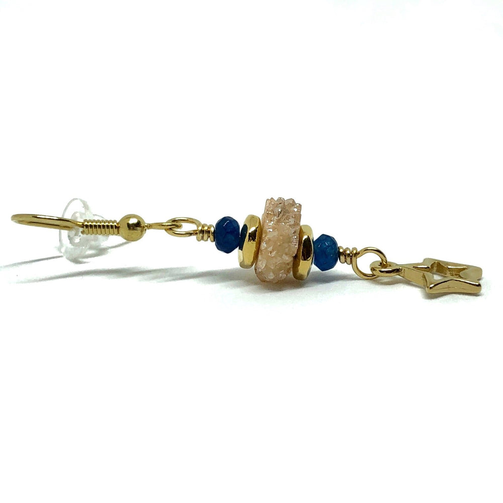 One earring lies on a white background and is pictured from a side view. The gold-toned earhook is to the left in the picture, and to it is attached a wire link on which are two indigo beads, two smooth, gold-toned beads, and, in the center, a champagne-colored druzy slice. At the other end of the wire link is a star charm, shown in profile.