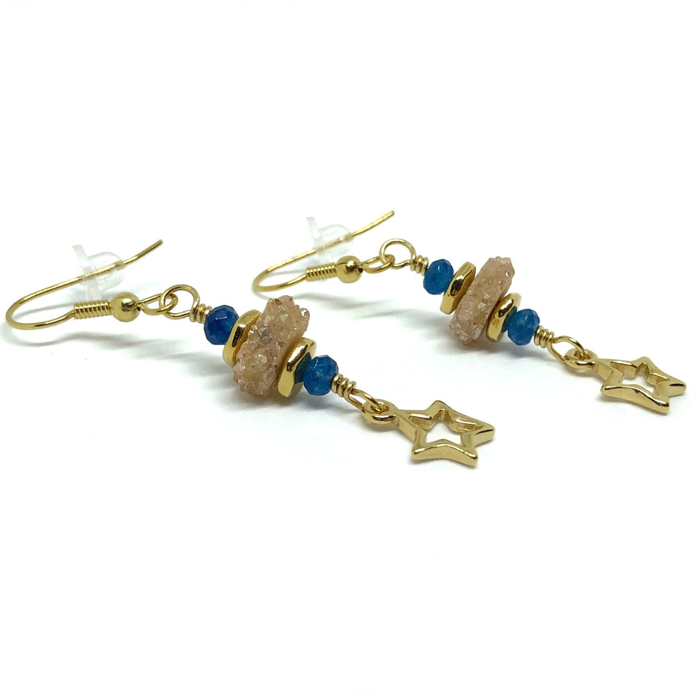Two earrings lie on a white background, viewed from the side and slightly above. Each gold-toned earhook is attached to a gold-toned wire link that features a slice of champagne-colored druzy sandwiched between smooth, gold-toned spacer beads. At each end is an indigo-blue faceted bead. The link is attached to a gold-toned open-star charm.