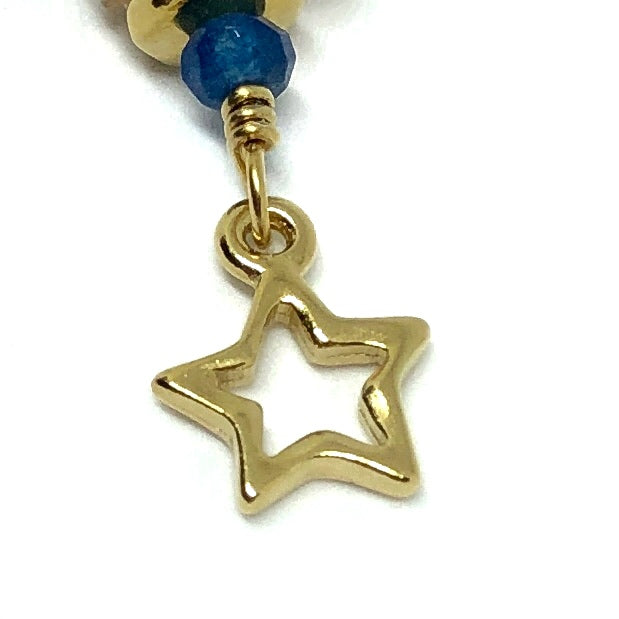 At the top of the photo is a partly visible gold-toned bead. Below it is a small blue bead, and below that is a wrapped loop of gold-toned wire. Attached to the loop is a gold-toned open-star charm, shown near the center of the photo. The background is white.