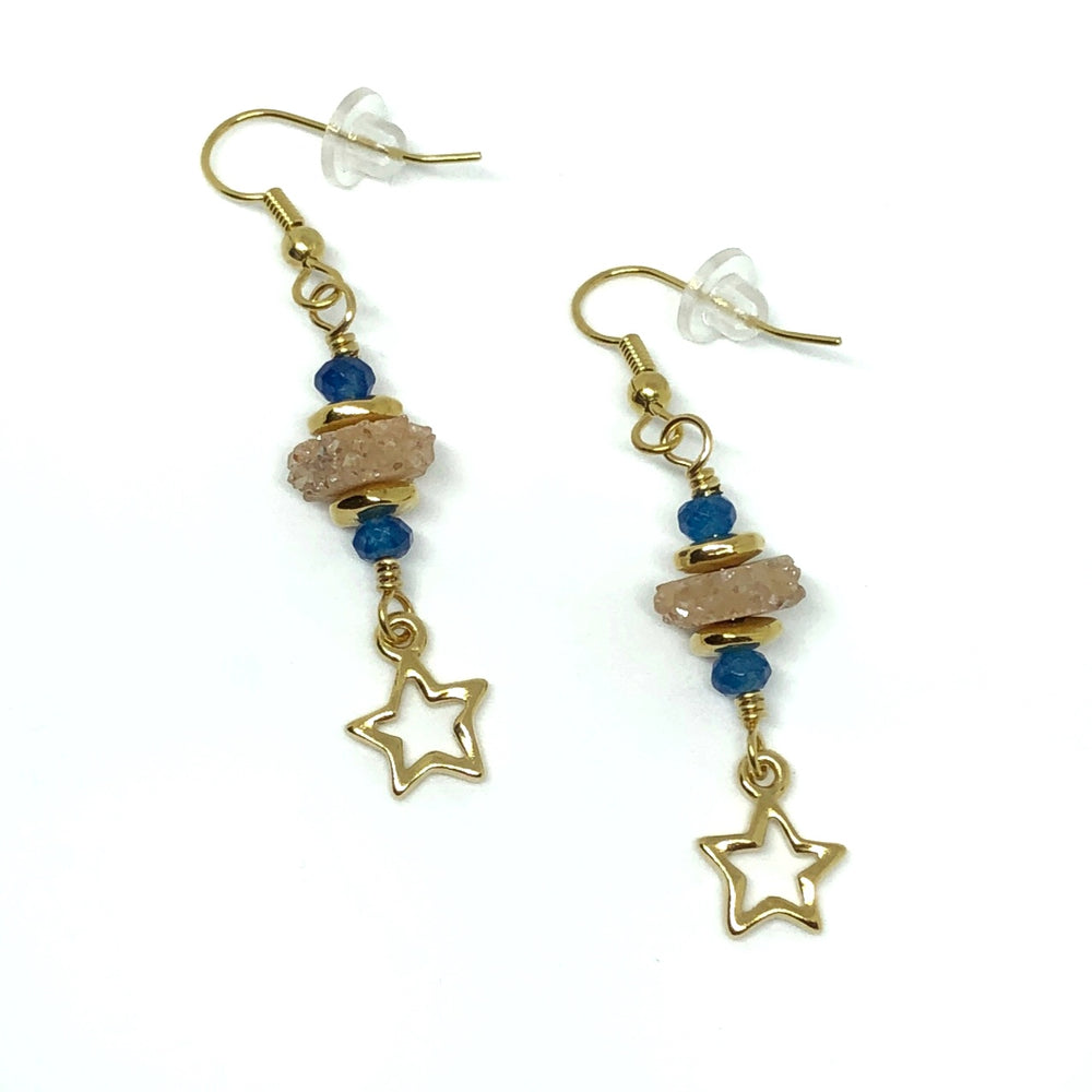 Two earrings lie on a white background. Each gold-toned earhook is attached to a gold-toned wire link on which is centered a champagne-colored slice of druzy. The druzy is sandwiched between two smooth, gold-toned spacer beads. Toward each end of the wire link is an indigo-blue faceted bead. The lower end of the link is attached to a gold-toned open-star charm.
