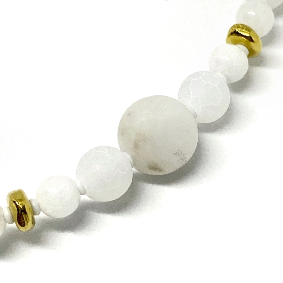 A strand of gold-toned metal spacer beads, round white beads, and tiny white spacer beads stretches from the lower left corner to the upper right, on a white background. The largest bead, in the center, has swirls of gray.