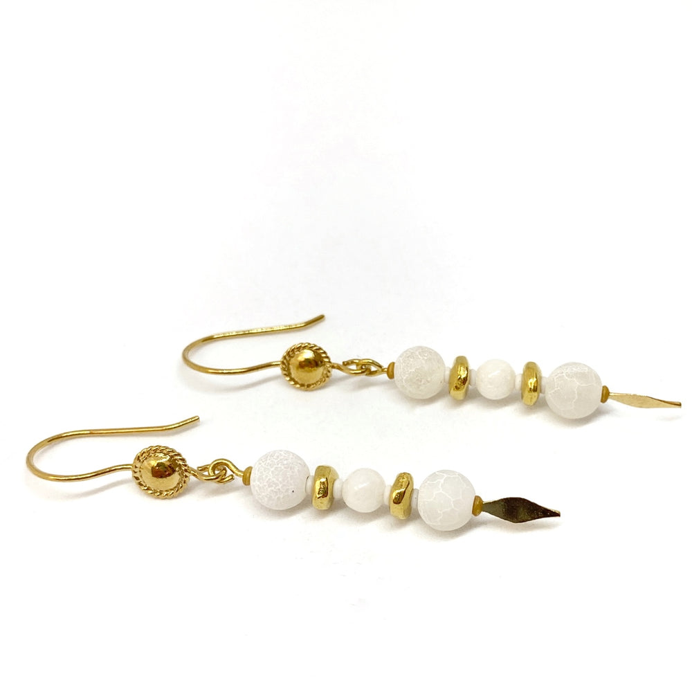On a white background lies a pair of earrings. To the left are the golden earwires, which feature medallion shapes, and from these wires dangle headpins with three white beads separated by golden metal beads and tiny white spacers. At the ends of the headpins are golden spear shapes.
