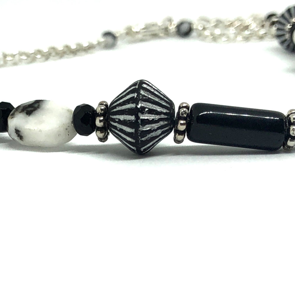 "Silver-toned, black, black and silver, and black and white beads in the STARSNOW Collection's ""Icicle Party"" necklace lie on a white background. Farther back, chain from the necklace is visible but out of focus."