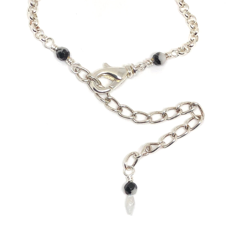 "The lobster-claw clasp, extender chain, and beaded dangle of the STARSNOW Collection's ""Icicle Party"" necklace lie on a white background. The metals are all silver-toned. Black and white beads adorn the dangle and the wire links that attach the clasp and chain to the rest of the necklace."
