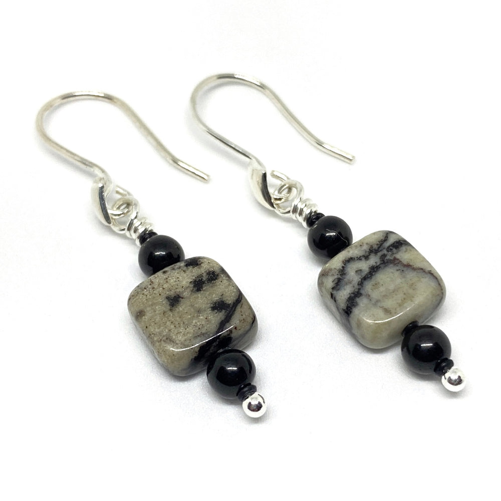 An earring lies on its side on a white background, the silver earwire to the left. On the dangle are two round black beads with a square beige and black bead in between. Small black spacers separate these beads.