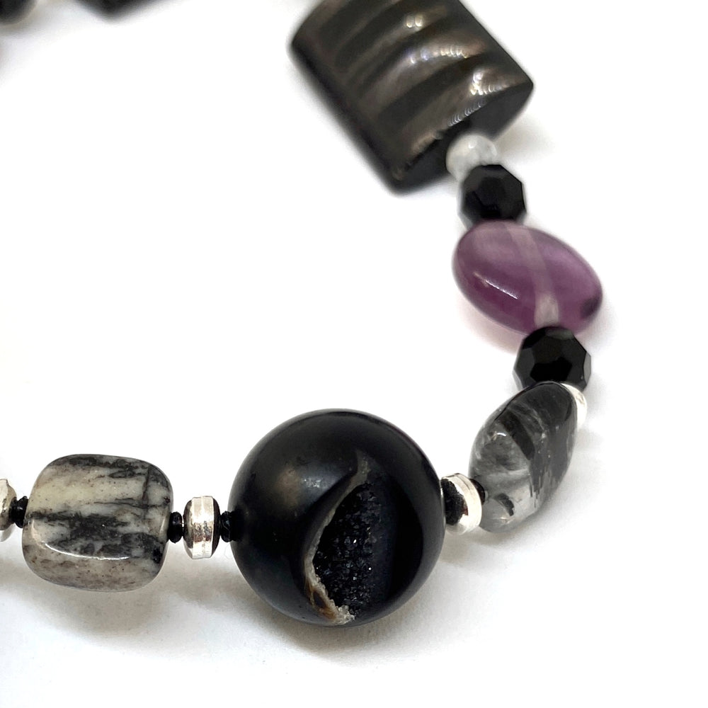 Part of a beaded strand of jewelry is visible. In the center foreground is a black bead with an opening inside which druzy can be seen. The other beads are silver, black, gray, and purple in color.