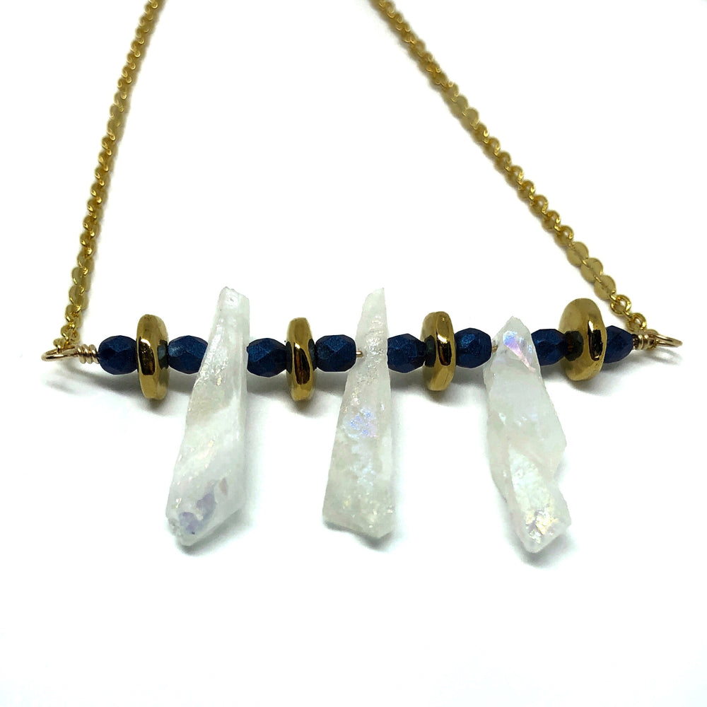 "The wire bar from the STARSNOW Collection's ""Snow at Sunset"" necklace stretches across the center of the photo, against a white background. Blue, gold-toned, and iridescent-white beads fill the length of the wire bar. From each end, small gold-toned chain extends to the top of the photo."