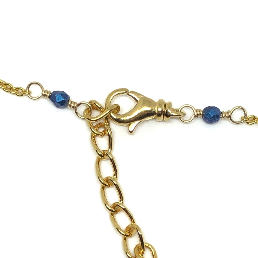 Near the center of the photo is a swivel lobster-claw clasp attached to a length of extender chain. Connected to the clasp and the chain are wire links, each with a small, faceted blue bead in the center of two wrapped loops. All the metals are gold-toned, and the background is white.