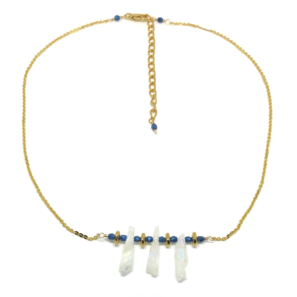 "The ""Snow at Sunset"" necklace from the STARSNOW Collection is pictured with the chain curved into a near-circle and the extender chain stretching from near the top of the photo almost to the center. The necklace features gold-toned chains and blue, gold-toned, and iridescent-white beads."