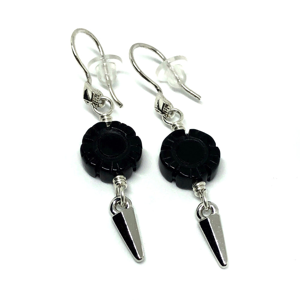 "The ""Starlit Garden"" earrings, from the STARSNOW Collection, lie on a white background. The earwires feature a diamond-shaped decoration and are sterling silver, as are the wire links that attach the other components. On each wire link is a flower-shaped black onyx bead. From each link hangs a silver-toned dagger charm."