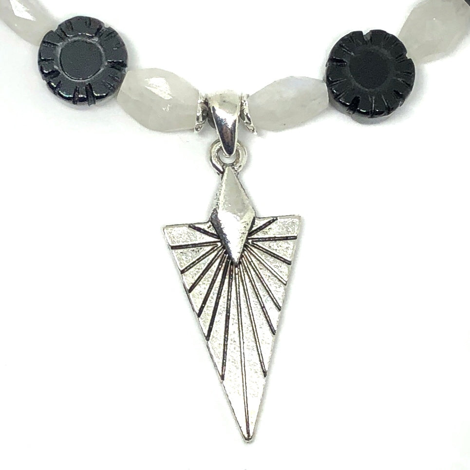 A beaded dangle sits in the center of the photo on a white background. The bead is a small, faceted black and white round. It is attached to a link of chain by a spear-shaped paddle pin. Both the pin and the chain are silver-toned.