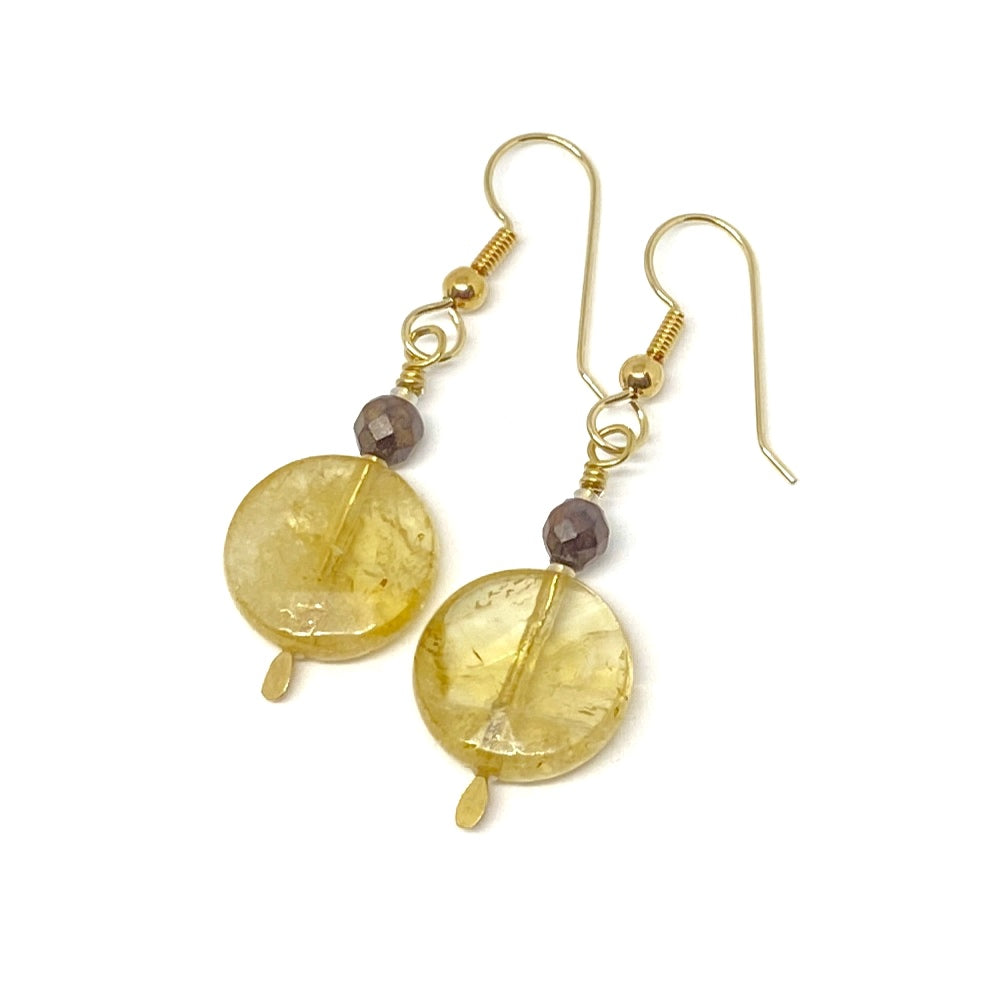 On a white background lies a pair of earrings. Each features a coin-shaped bead in a deep golden-yellow, topped by a small faceted wood bead and a golden earwire.
