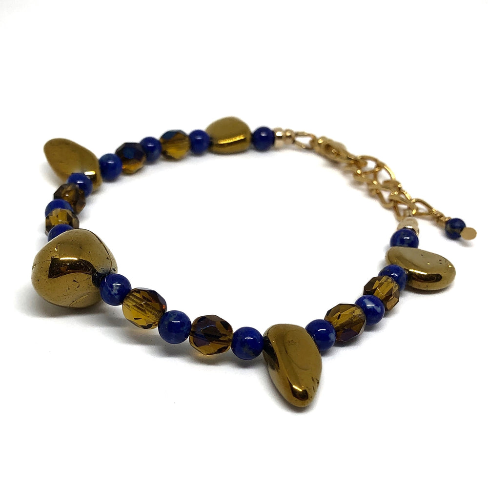 "On a white background, the ""Twilight Gathering"" bracelet from the STARSNOW Collection is pictured from above and to the side. Visible are the extender chain, lobster-claw clasp, and beads in blue, golden, and honey tones."