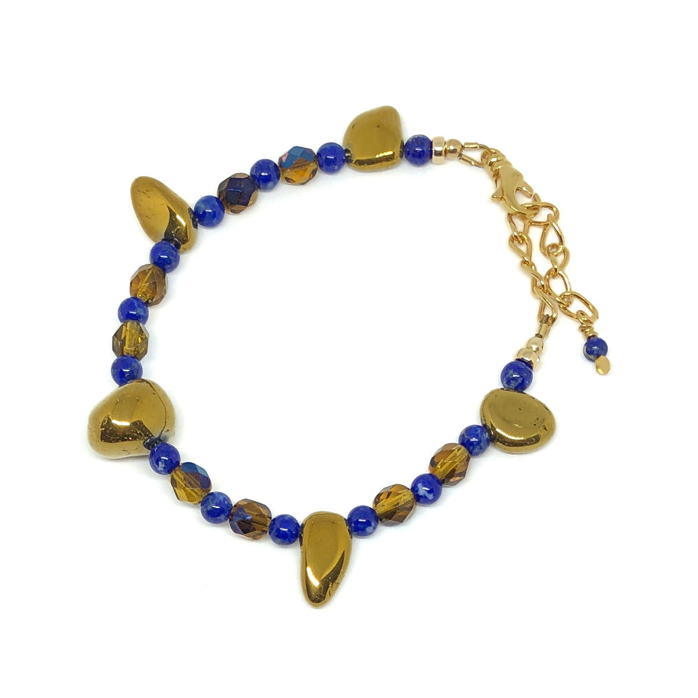 "The ""Twilight Gathering"" bracelet from the STARSNOW Collection lies on a white background. The bracelet features a gold-plated extender chain and lobster-claw clasp. Five larger, irregularly shaped golden beads are separated by smaller, alternating blue and blue-and-honey-colored beads."