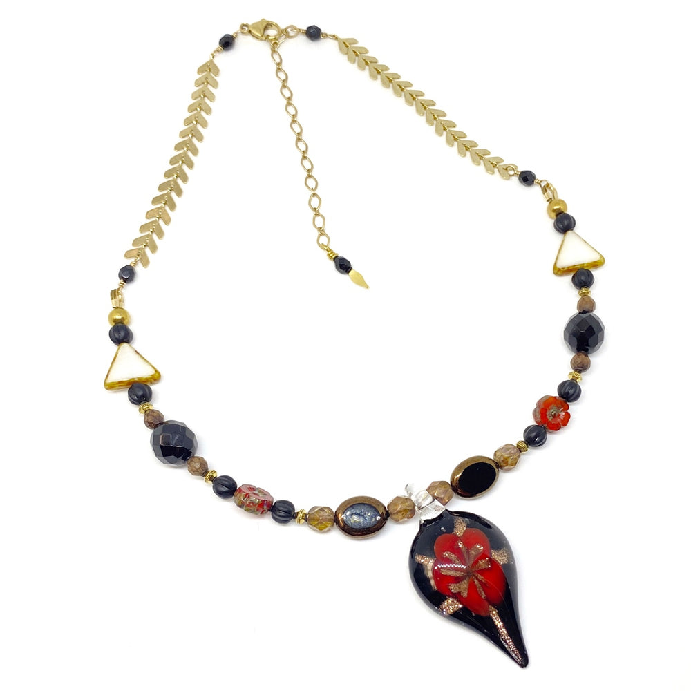 A pendant necklace featuring golden chevron chain and beads in black, brown, and red lies on a white background. The necklace is clasped, and the extender chain points down toward the pendant.