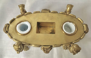 Regency period gilt bronze inkstand raised on lioness paw feet and adorned with ram masks.