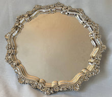 Large silver plated circular salver with shell and scroll border, raised on bun feet.