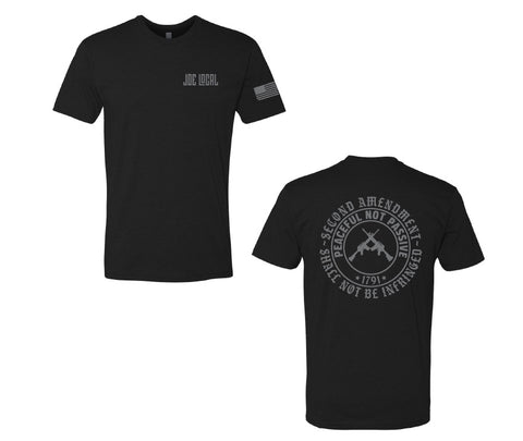 "Black cotton short sleeve t-shirt. Joe Local logo on left pocket. The back of the t-shirt has a circular logo saying ""second amendment shall not be infringed. Also, within that circle is another circle with the phrase ""peaceful not passive, 1791"". Within that circle at the center are Two guns in center crossing each other"