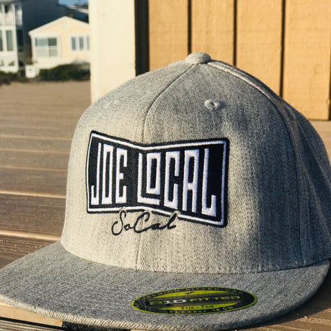 Gray flat bill cotton cap. Black and white embroidered Joe Local So Cal flag logo. Flex fit, premium fitted cap