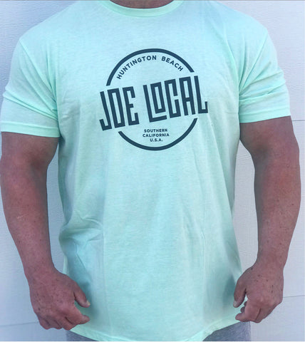 Front of the t-shirt. Joe Local Classic short sleeved Tee In Mint green with Joe Local Huntington Beach/So Cal Circled Logo. Joe Local Logo on upper back centered under the neck.