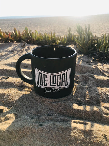 Joe Local 12oz Coffee Mug. Black ceramic mug with white Joe Local So Cal flag logo. Handle is shaped in a half circle allowing for room for your fingers. The mug has a solid  and heavy feel. The mug is round in shape from top to bottom of the mug.