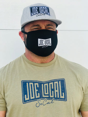 Joe Local Black cotton face mask. Attaches at ears. Covers face from nose to under chin. Picture also features Joe Local flat billed hat and Joe Local original logo t-shirt in olive green.