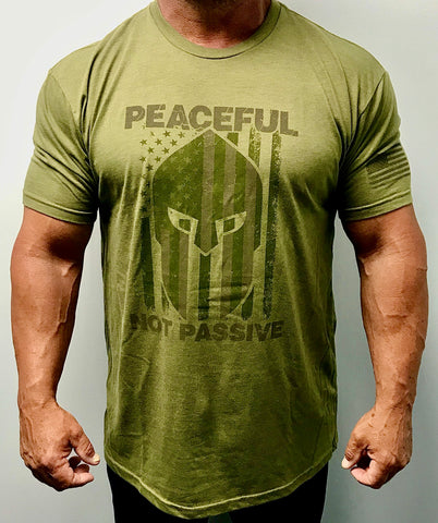 "60% Cotton, 40% Poly. Military green Crew neck. shirt has a large screen print in greenish brown. logo is of a warrior helmet layered over and American flag. phrase ""Peaceful Not Passive. The word ""peaceful"" is located at top of the flag/helmet and the words ""not passive"" is featured at bottom of the flag/helmet. back of the t-shirt features small simple ""Joe Local"" logo across top of t-shirt under the neck. left sleeve features a small screen print of the American flag in greenish brown."