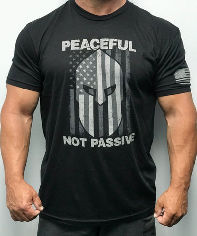 "60% Cotton, 40% Poly. Black Crew neck. shirt has a large screen print in white. logo is of a warrior helmet layered over and American flag. phrase ""Peaceful Not Passive. The word ""peaceful"" is located at top of the flag/helmet and the words ""not passive"" is featured at bottom of the flag/helmet. back of the t-shirt features small simple ""Joe Local"" logo across top of t-shirt under the neck. left sleeve features a small screen print of the American flag in white."