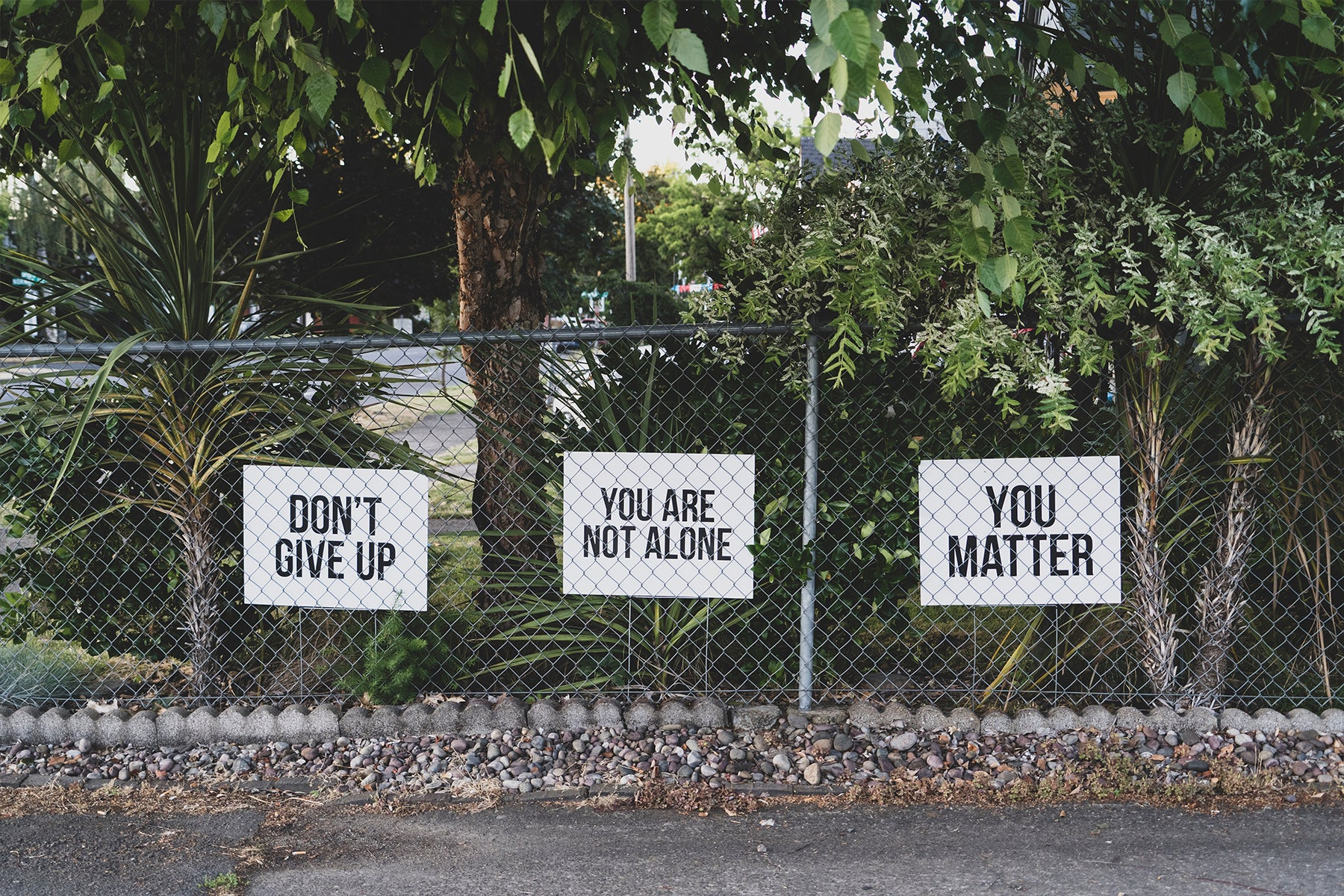 3 signs behind a chain link fence reading, Don't Give Up, You Are Not Alone, You Matter