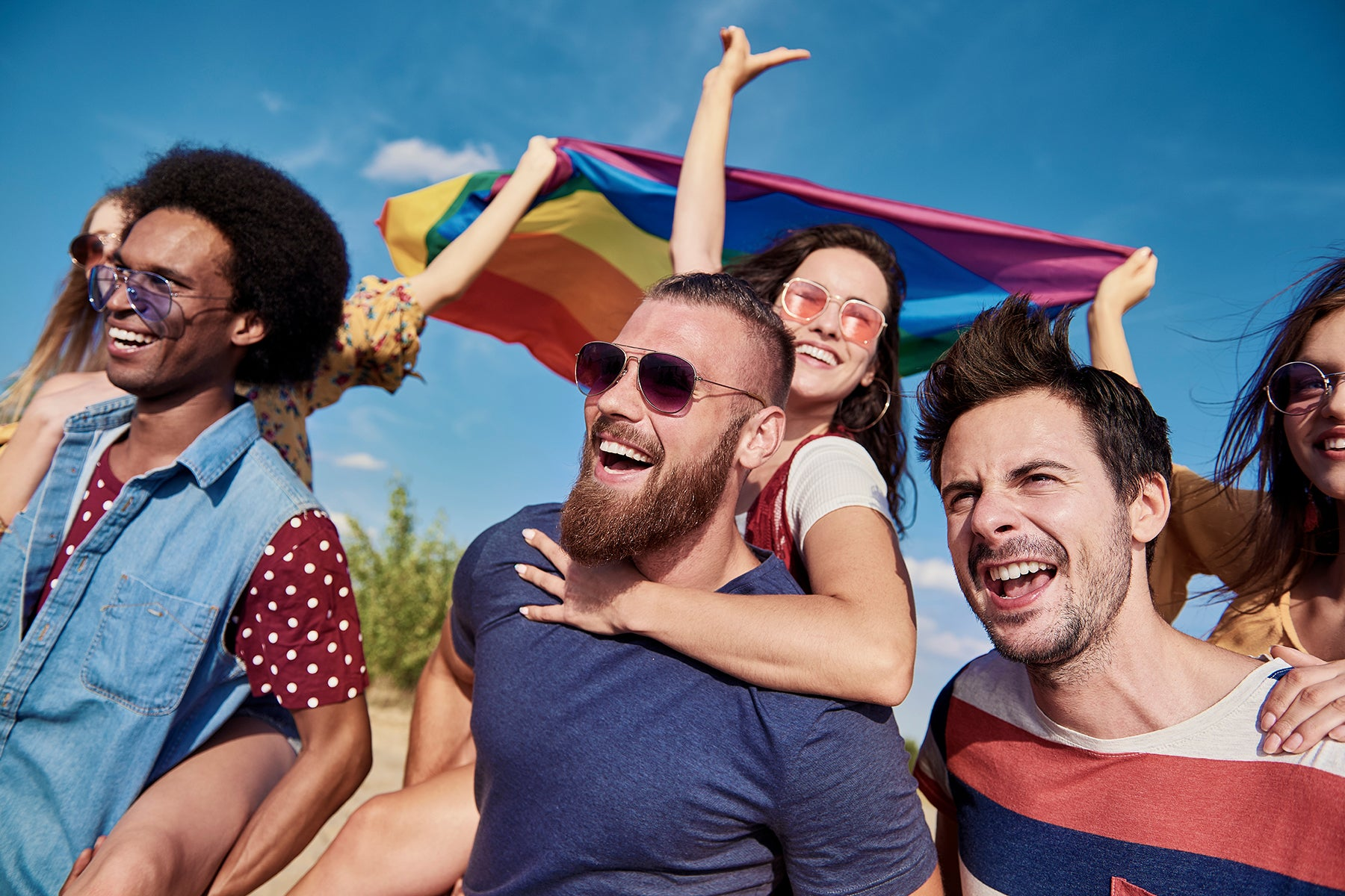 A group of friends celebrating pride, holding a rainbow flag in the air.