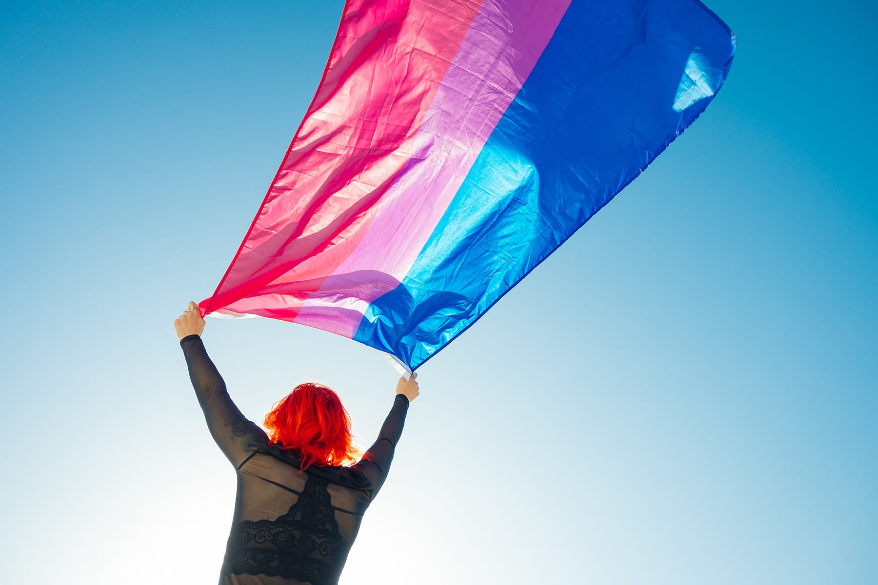 A white person with bright red hair facing away from the camera. They are holding a bisexual flag above their head.