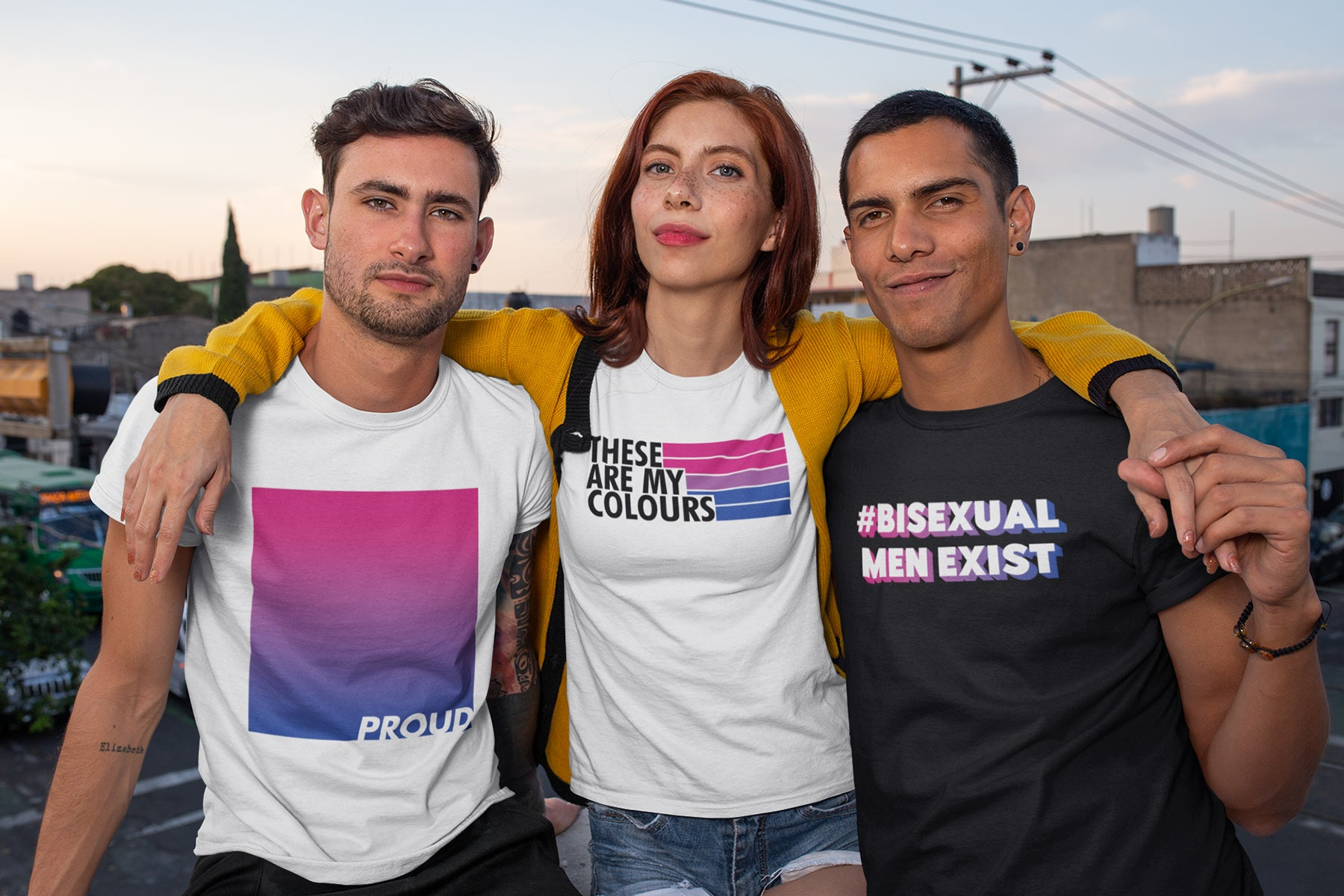 A group of 3 friends all wearing Bisexual themed Rainbow & Co shirts. The first person is a white man with brown hair wearing a white shirt featuring a bisexual flag gradient and the word PROUD, the second person is a white woman with red hair and lipstick wearing a white shirt featuring the bisexual flag and the words THESE ARE MY COLOURS, the third person is a brown man wearing a black shirt with the hashtag #BisexualMenExist.