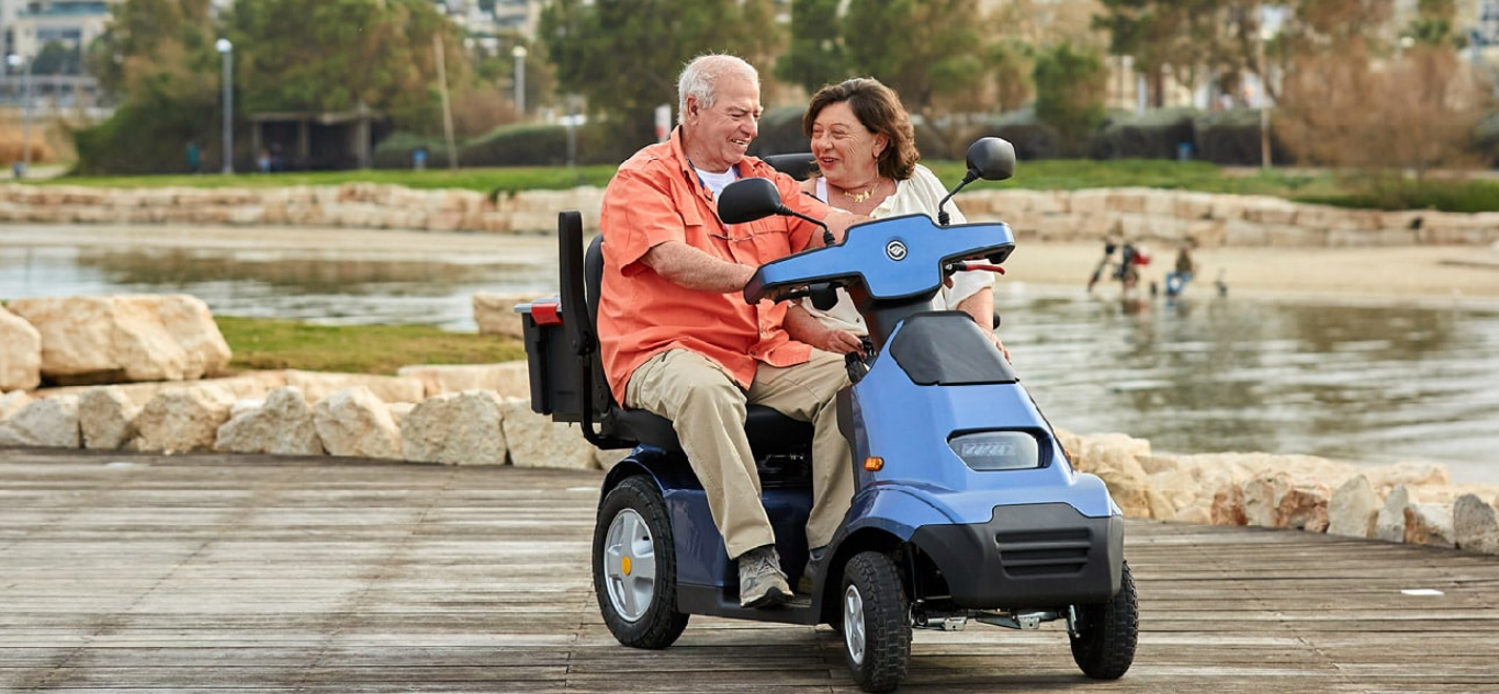 2-seater mobility scooter with elderly couple at park