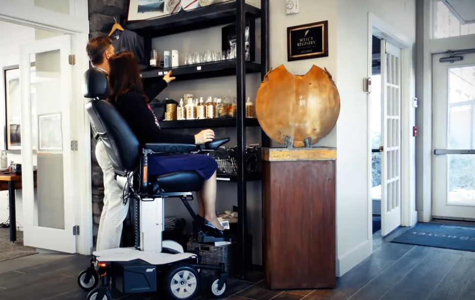 reaching up to regular items at home cupboards on electric wheelchair