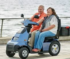 2-people on mobility scooter at the beach