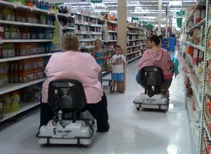 shoppers using disable powered carts in supermarket aisle