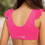 Girls two piece eco-friendly reversible pink bikini swimsuit with ruffle detail.