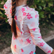 Girl wearing eco-friendly pink floral long sleeve rashguard with ruffles