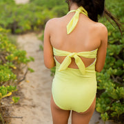 Girl wearing yellow swimsuit with back and neck ties