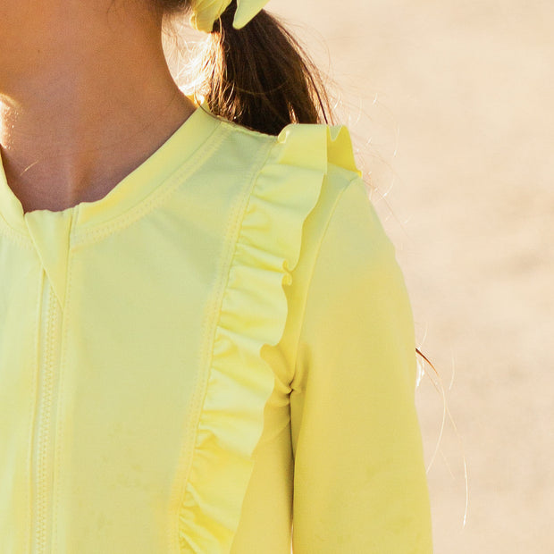 Girl's eco-friendly long sleeve vibrant yellow rash guard.